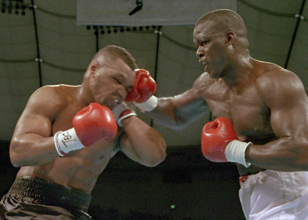 """James """"Buster"""" Douglas, right, hits Mike Tyson with a hard right in the face during t ..."""