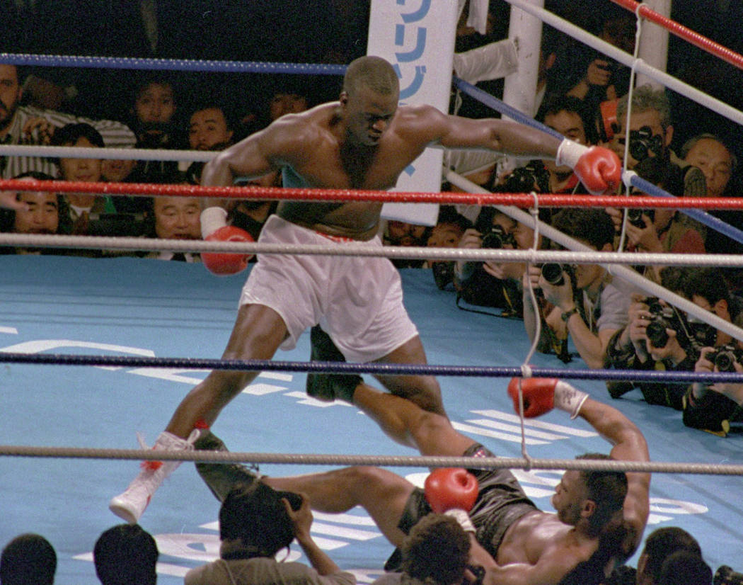 """Challenger James """"Buster"""" Douglas, stands over champion Mike Tyson who fell on his back after t ..."""
