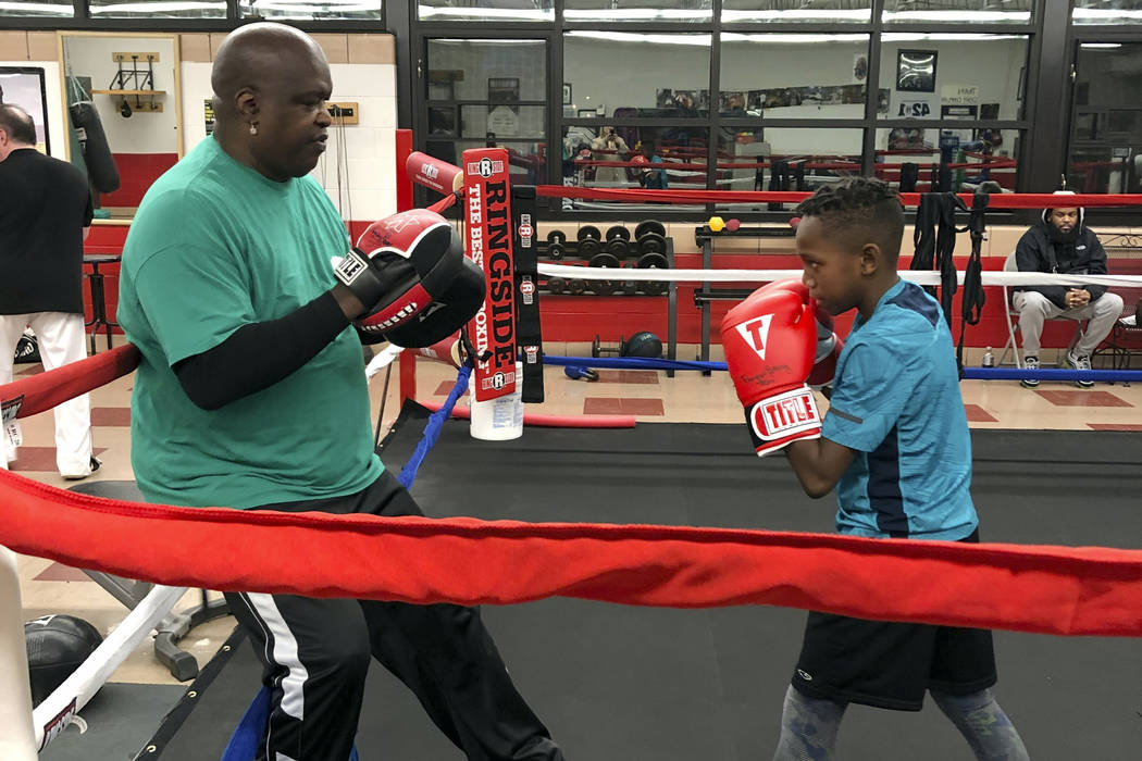 """James """"Buster"""" Douglas, the former world heavyweight champion, works with a student at the Thom ..."""