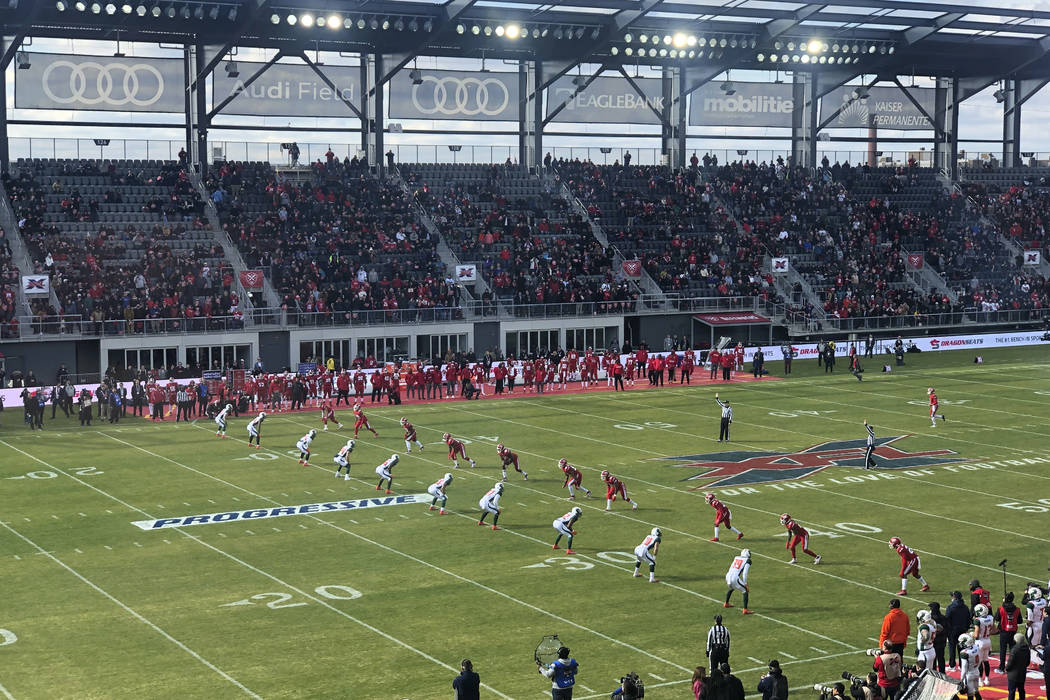 The D.C. Defenders, right, line up against the Seattle Dragons for the opening kickoff of the o ...
