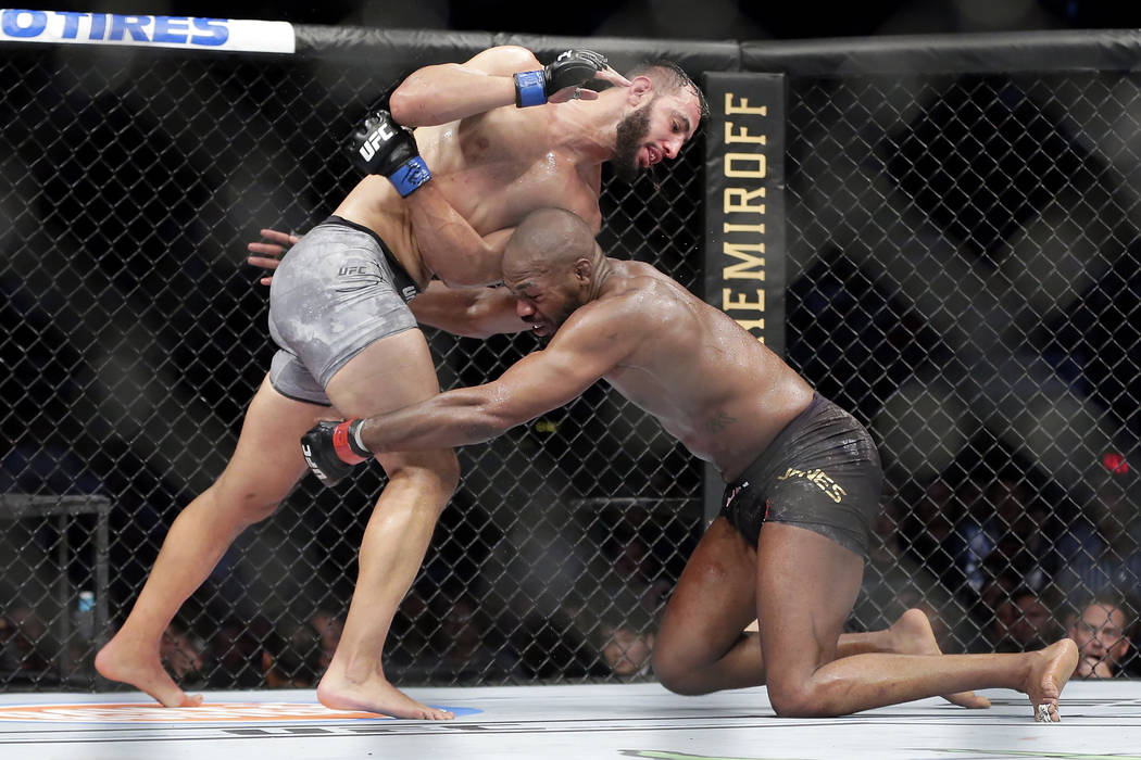Jon Jones, right, goes for a take down of Dominick Reyes, left, during a light heavyweight mixe ...