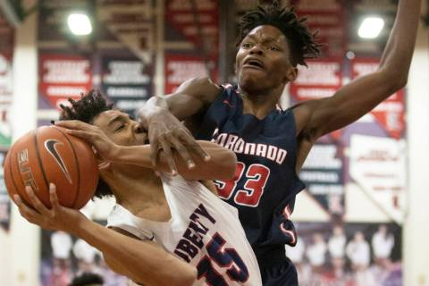 Liberty junior forward Greyson Montgomery (15) gets fouled on the way to the rim by Coronado so ...