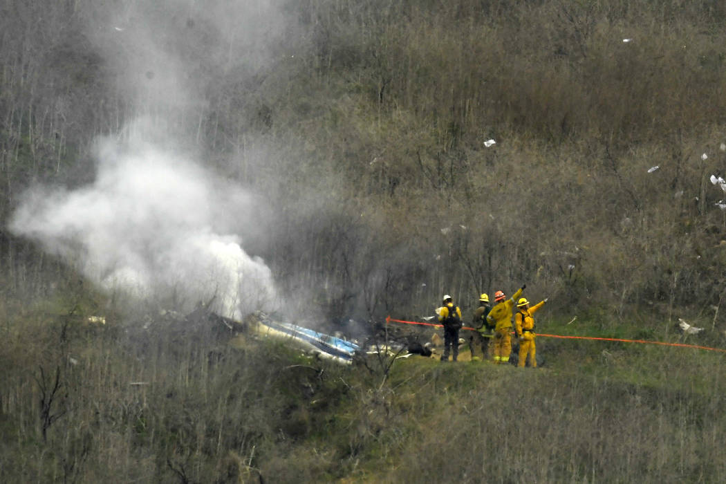 FILE - In this Jan. 26, 2020 file photo firefighters work the scene of a helicopter crash where ...
