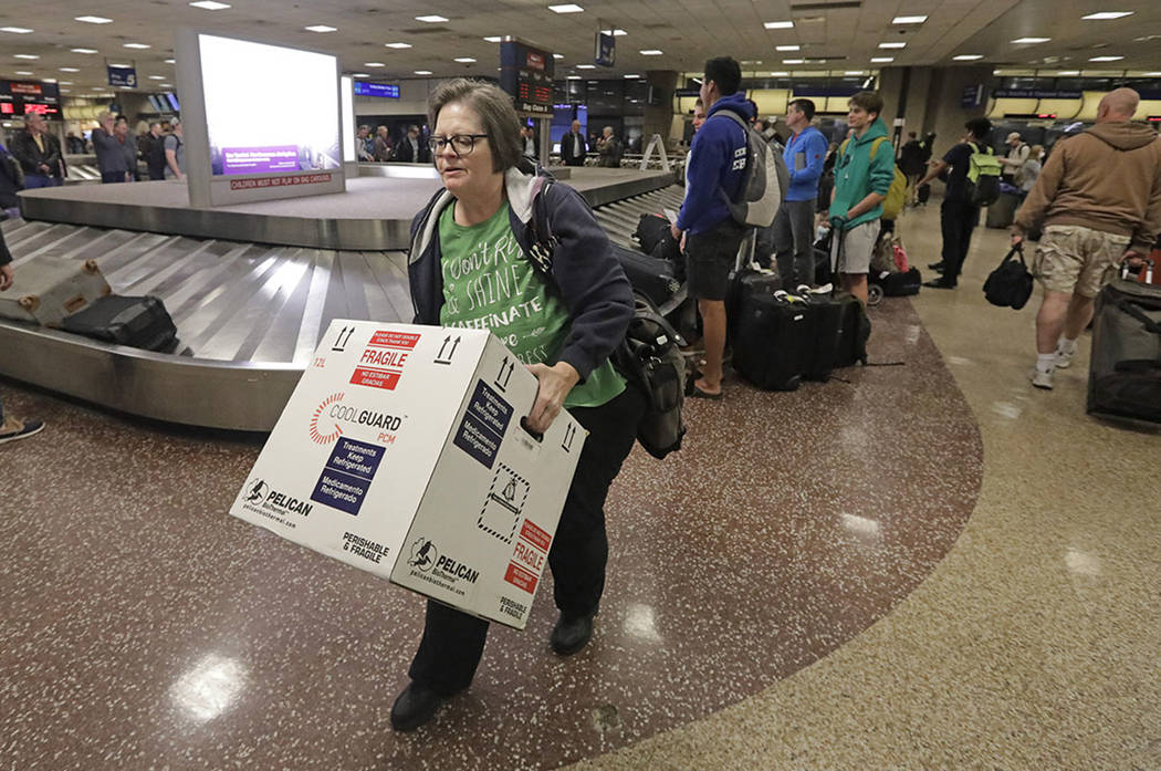 Ann Lovell carries her box of prescriptions after returning to Salt Lake City International Air ...
