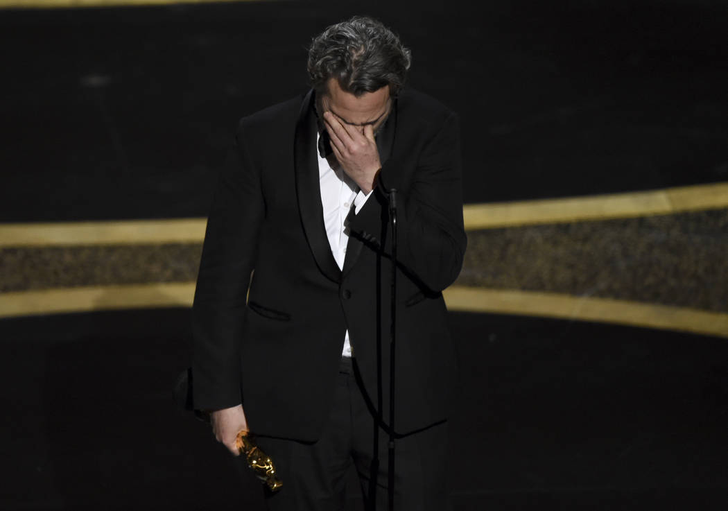 Joaquin Phoenix reacts as he accepts the award for best performance by an actor in a leading ro ...