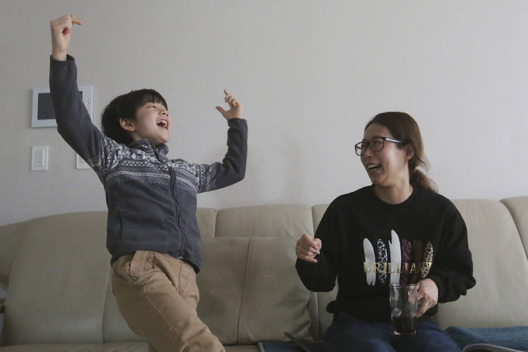 Parasite actor Jeong Hyeonjun, left, and his mother Lee Min Jae celebrate as they watch a TV li ...