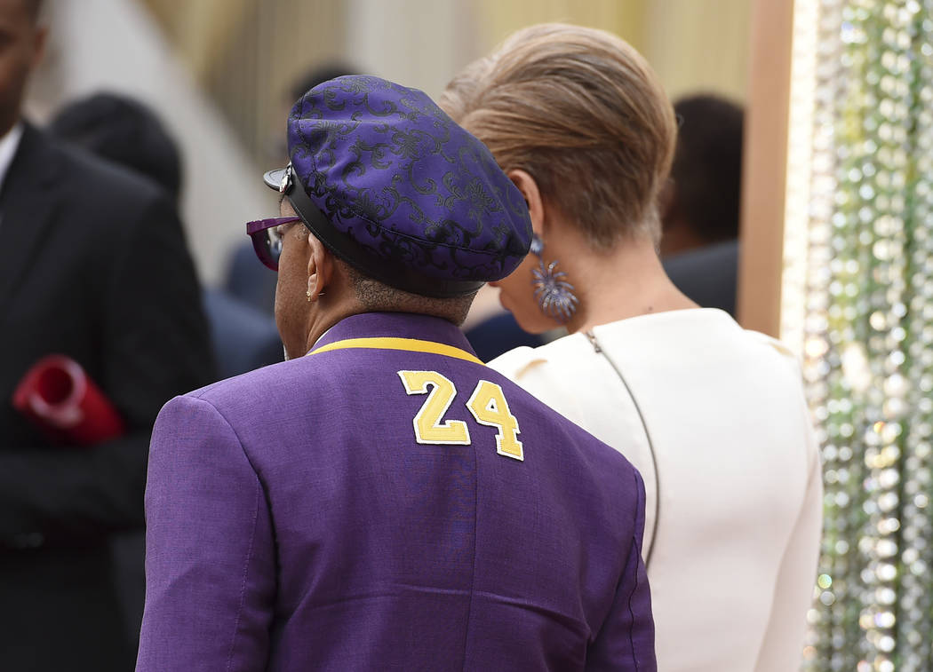 Spike Lee, left, wearing a jacket with the number 24 in honor of the late Kobe Bryant, and Tony ...