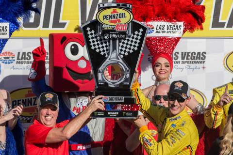 Joey Logano, right, and Carlos Maurer, president of Shell Lubricants Americas, hold the first p ...