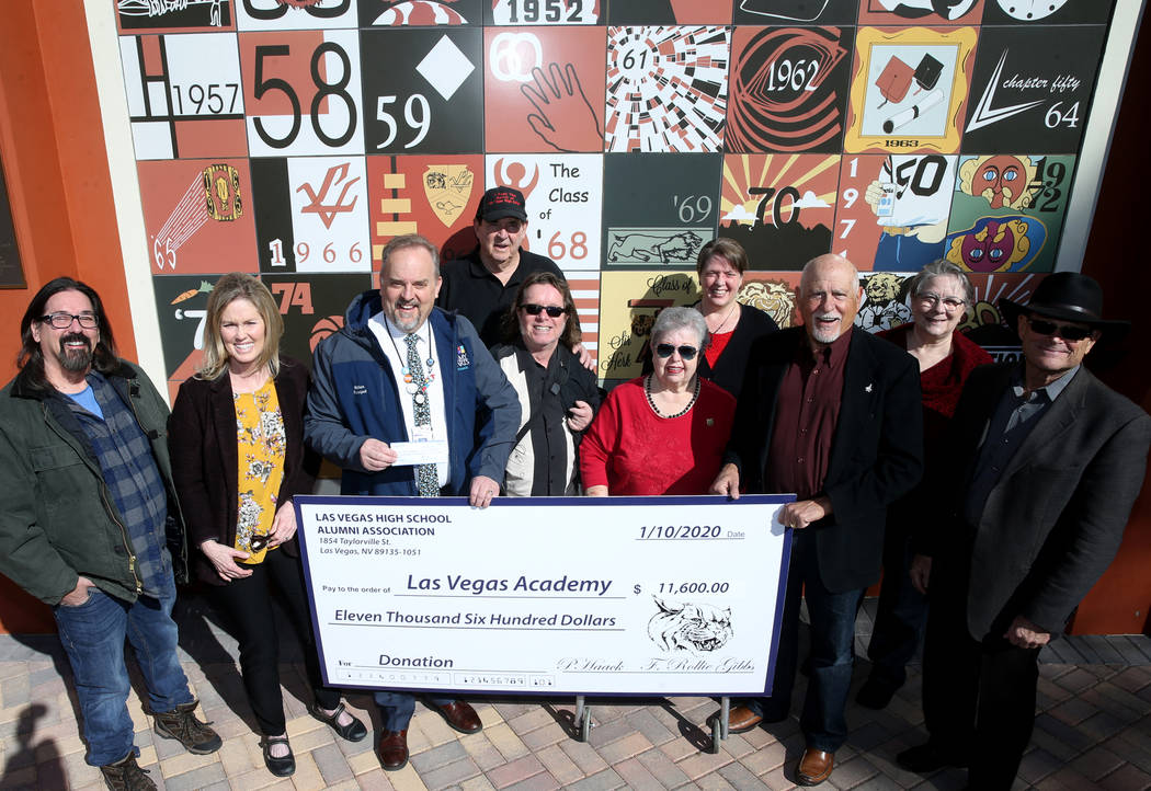 Las Vegas Academy principal Scott Walker, third from left, poses with alumni, from left, Joe Th ...