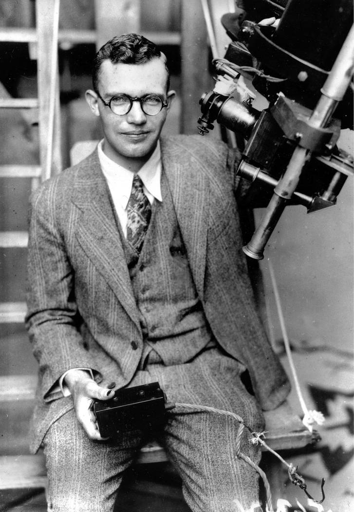 In this 1931 file photo, Clyde Tombaugh poses with the telescope through which he discovered th ...