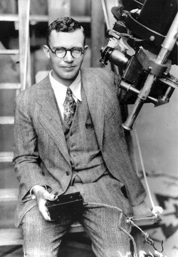 Clyde Tombaugh poses with the telescope through which he discovered the Pluto at the Lowell Obs ...