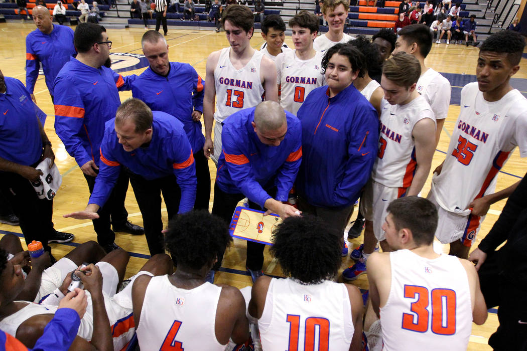 Bishop Gorman coaches talk to their players before the start of the fourt quarter of their bask ...