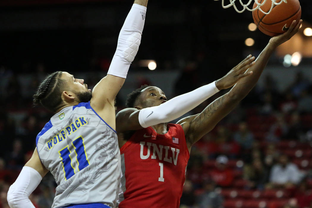 UNLV Rebels guard Kris Clyburn (1) takes a shot while under pressure from UNR Wolf Pack forward ...