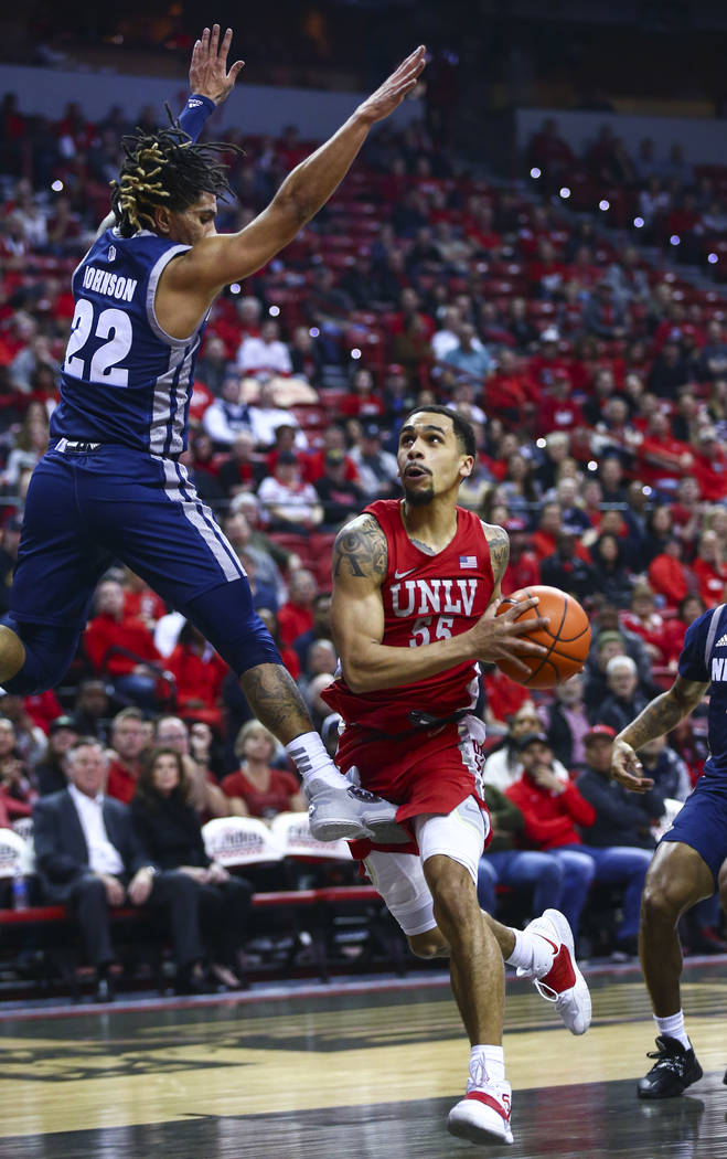 UNLV's Elijah Mitrou-Long (55) drives to the basket as UNR's Jazz Johnson (22) defends during t ...