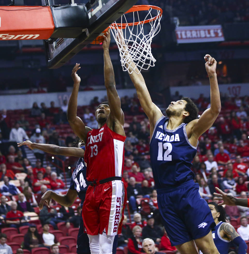 UNLV's Bryce Hamilton (13) goes to the basket against UNR's Johncarlos Reyes (12) during the fi ...