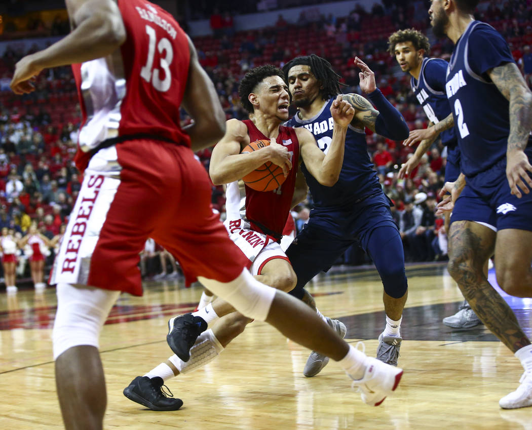 UNLV's Marvin Coleman (31) drives to the basket against UNR's Jazz Johnson (22) during overtime ...