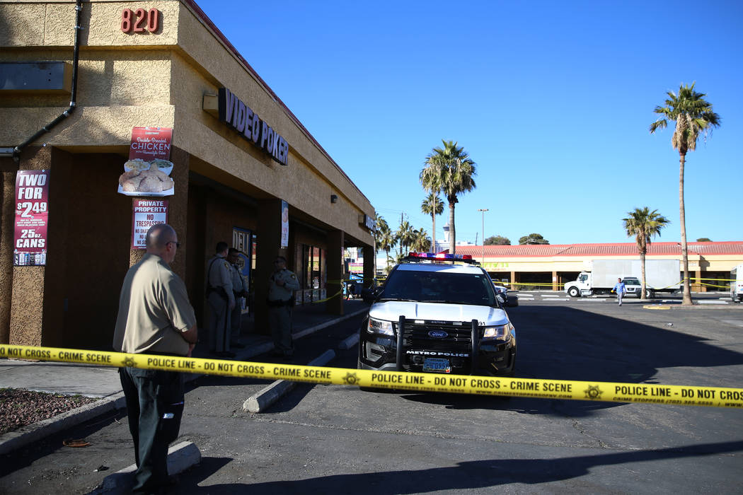 Police investigate a homicide in a shopping center at the intersection near Swenson Street and ...