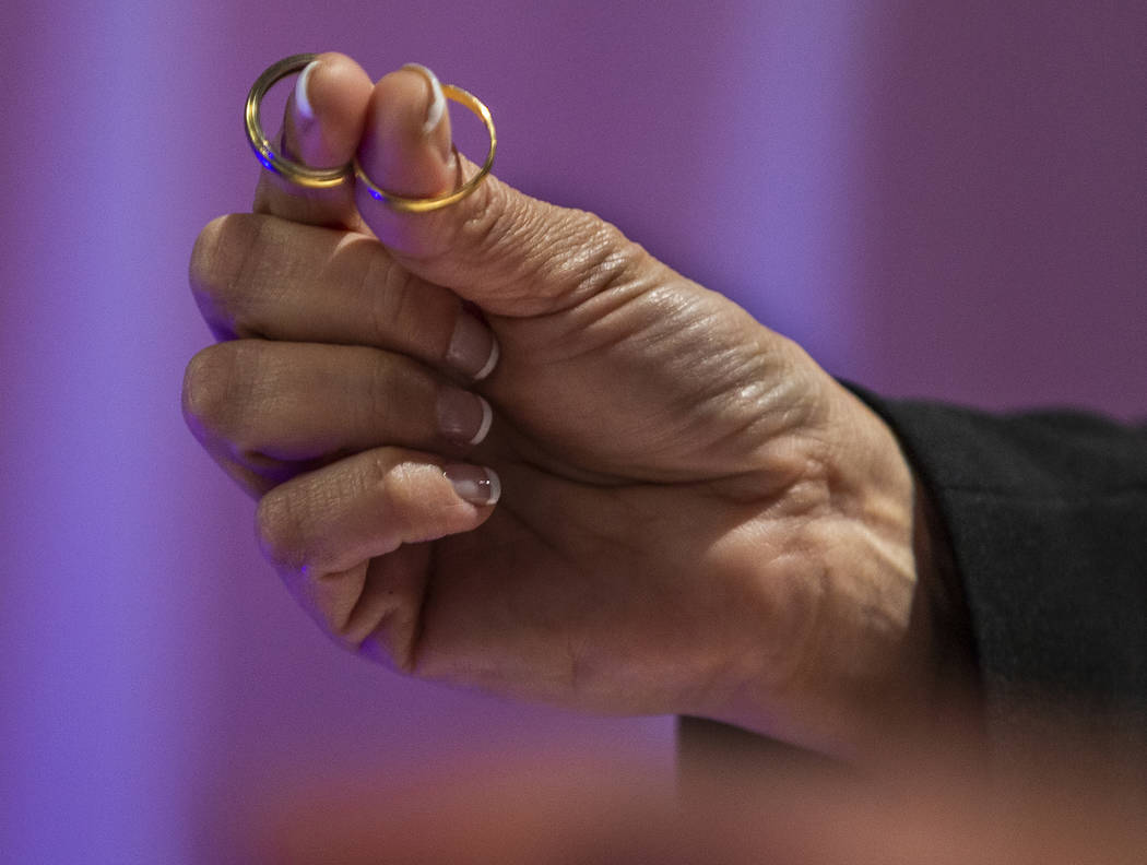 The Rev. Diana Moran holds the rings of Corrine and Aristide Justeau visiting from France as sh ...