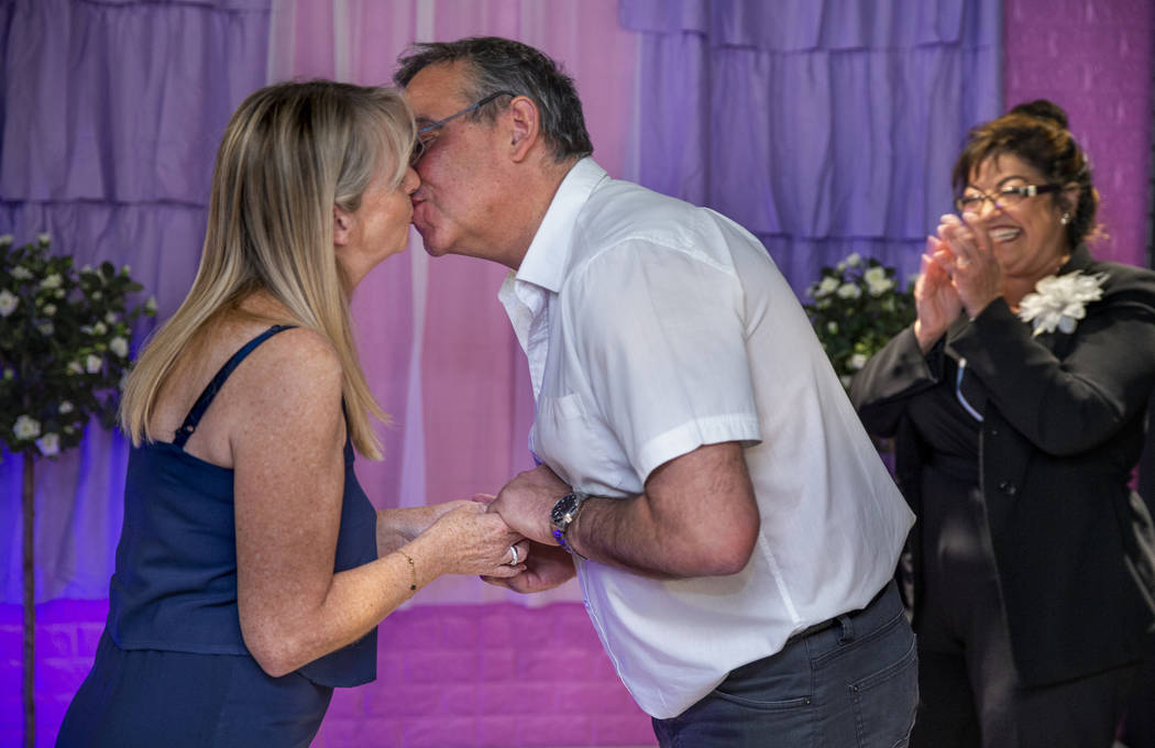 Corrine Justeau, left, and husband Aristide visiting from France kiss after their wedding renew ...
