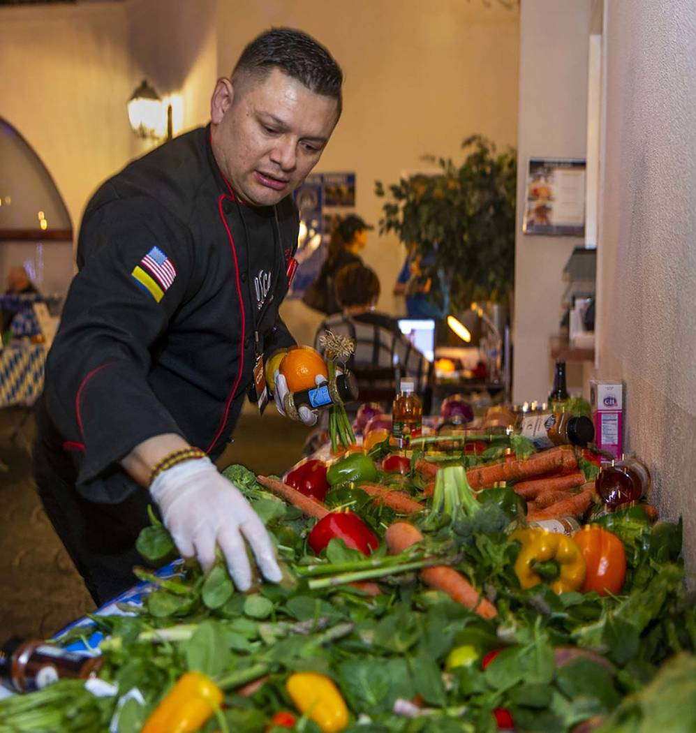 Chef Oscar Sanchez, Chef Battle Las Vegas winner, grabs more vegetables from the pantry as time ...