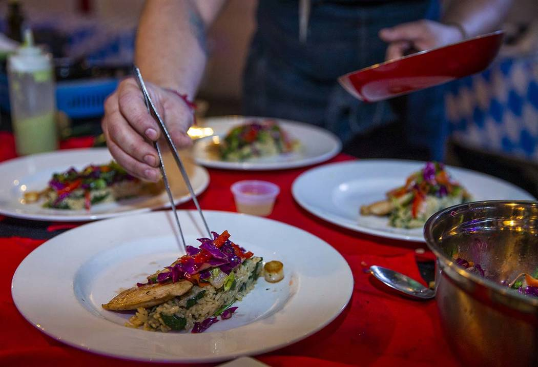 Sous chef Ron Sapp arranges mushrooms with a tweezer while working with Chef Battle Las Vegas w ...