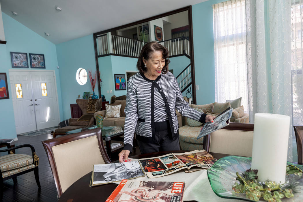 Moulin Rouge dancer Anna Bailey looks at her photographs printed in Life Magazine, in her home ...