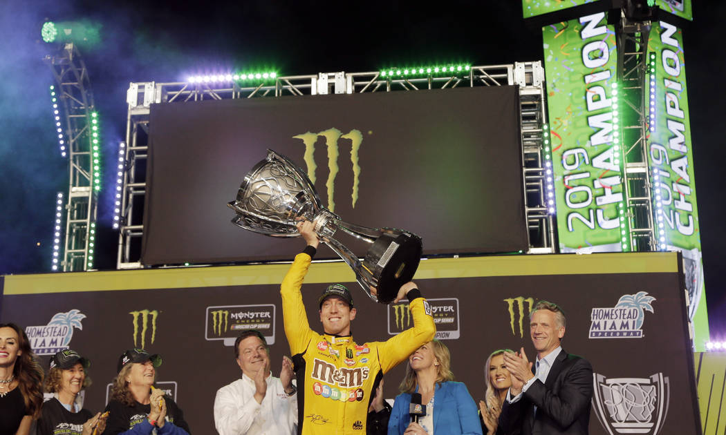 FILE - In this Nov. 17, 2019, file photo, Kyle Busch, center, holds up his trophy in Victory La ...
