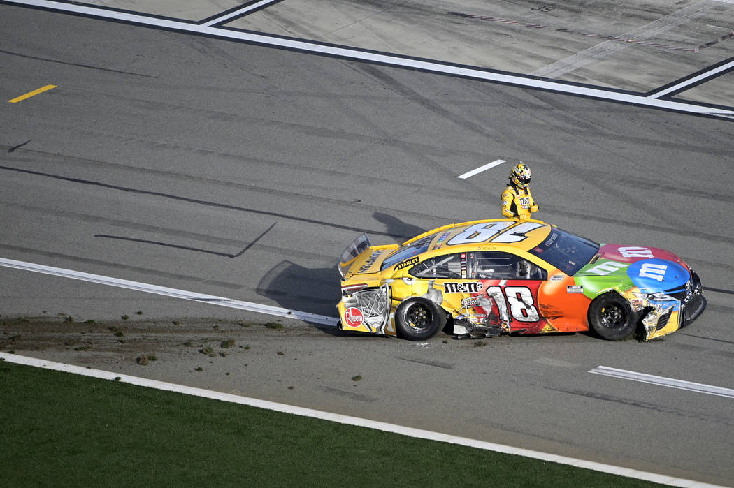 Kyle Busch (18) climbs out of his car after coming to a stop on pit road after colliding in Tur ...