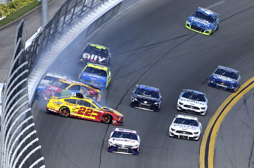 Joey Logano (22), Kyle Busch (18) and Brad Keselowski (2) collide in Turn 4 during the NASCAR D ...