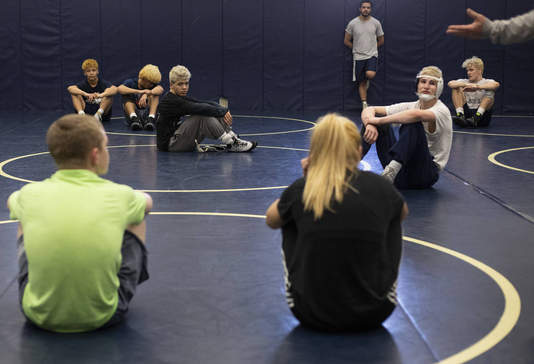 The wrestling team from Shadow Ridge High School listens to coaching staff at the end of practi ...