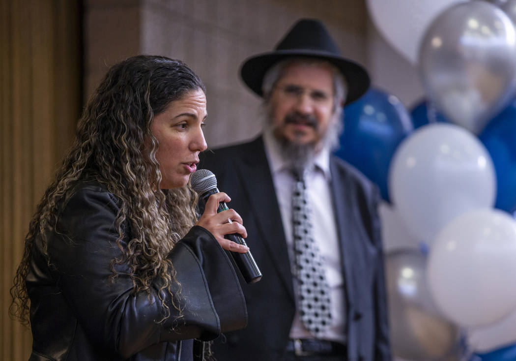 Taly Furer speaks about her deceased father Mordechai Bitton beside Rabbi Shea Harlig as they r ...