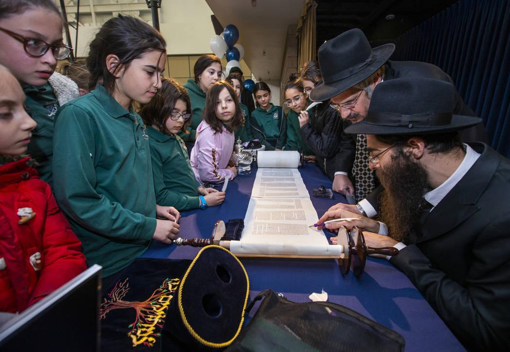 Rabbi Dovid Bressman, bottom right, as Sofer with Rabbi Shea Harlig, above, inscribes the new T ...