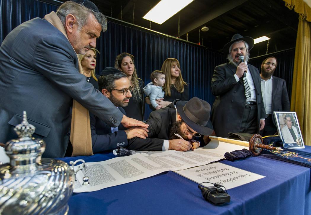 Rabbi Dovid Bressman, center, as Sofer inscribes the last words on a new Torah surrounded Rabbi ...