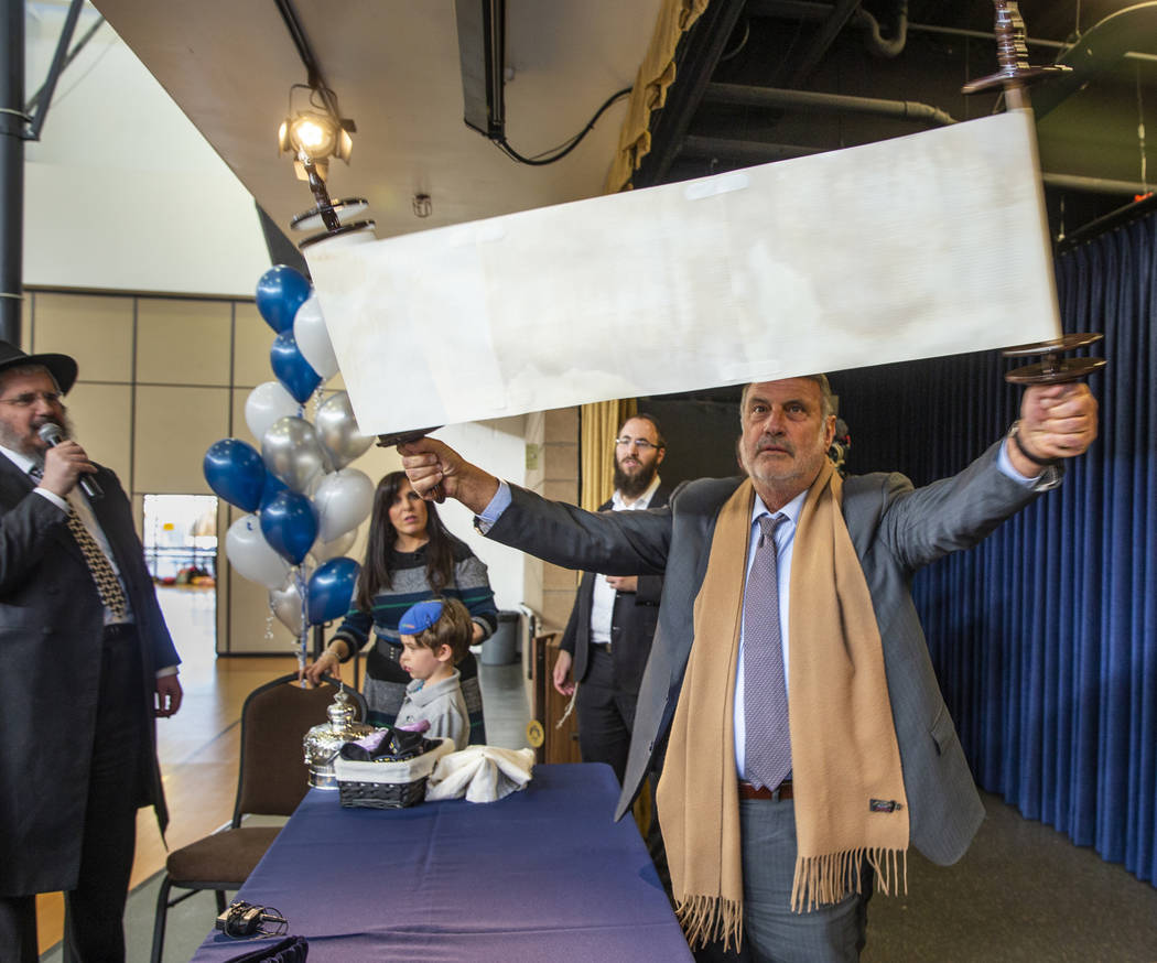 Sonny Kahn, right, shows off a newly inscribed Torah to all in attendance at a ceremony for it ...