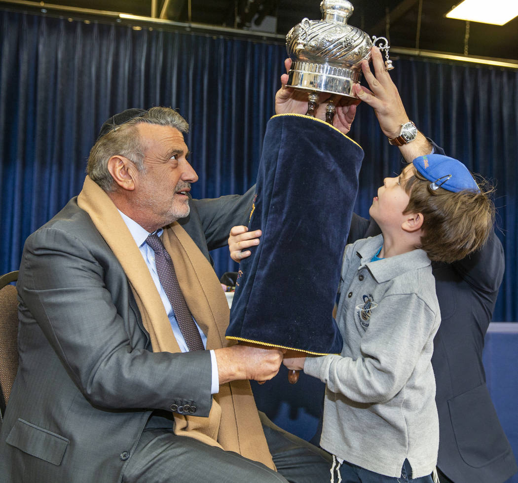 Sonny Kahn, left, holds a newly inscribed Torah with the help of student Eitan Yafee, 6, at the ...
