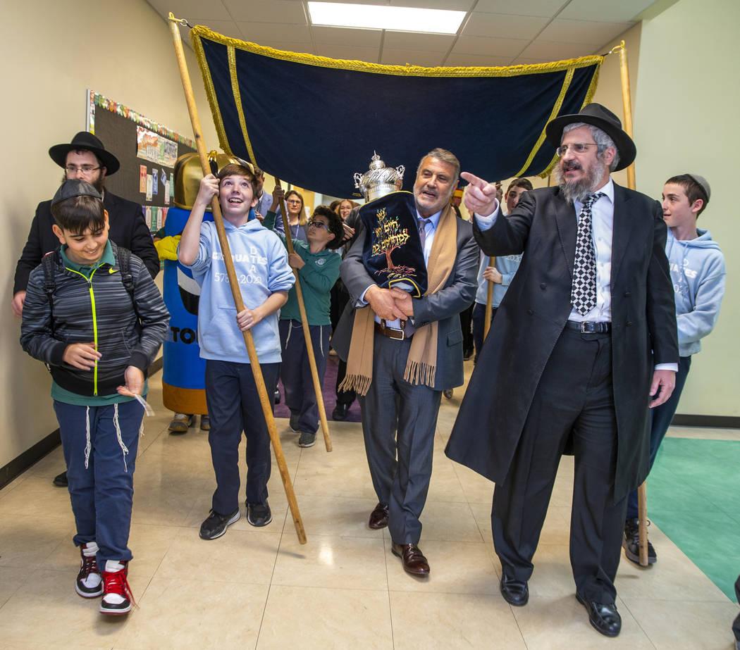 Sonny Kahn, center, carries a newly inscribed Torah beside Rabbi Shea Harlig, right, as they pr ...
