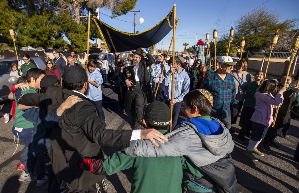 Chabad of Southern Nevada members march and dance while carrying their new Torah about the neig ...