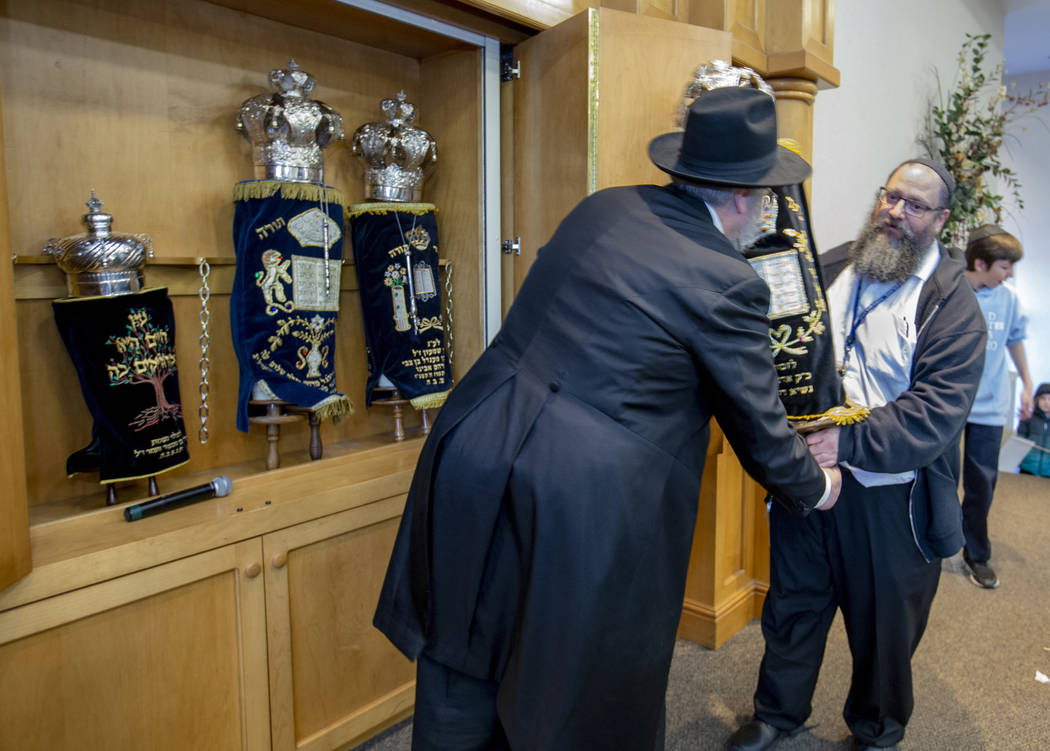 Rabbi Shea Harlig, left, puts away their new Torah joining the three existing ones in their syn ...