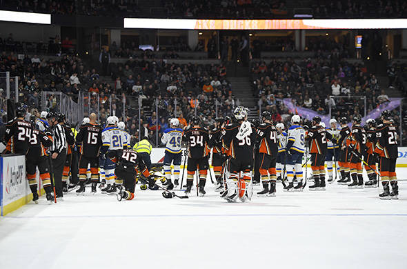 Members of the St. Louis Blues and Anaheim Ducks gather on the ice as Blues defenseman Jay Bouw ...