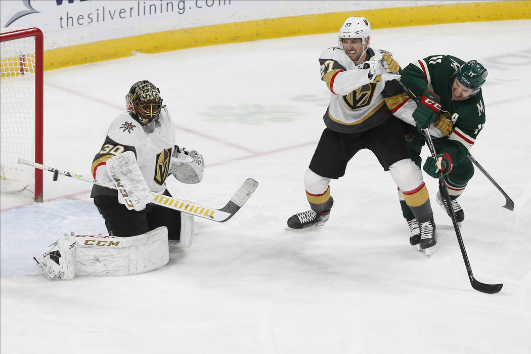 Vegas Golden Knights' Shea Theodore, second from right, keeps Minnesota Wild's Zach Parise in c ...