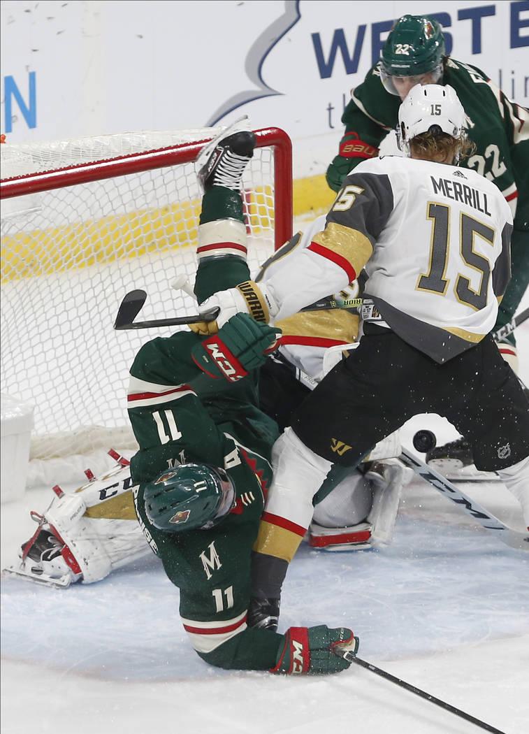 Minnesota Wild's Zach Parise, left, gets upended at the net by Vegas Golden Knights' Jon Merril ...