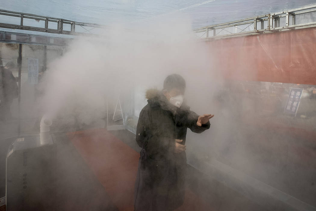 A man walks through a disinfectant spray in order to return home at a residential complex in no ...