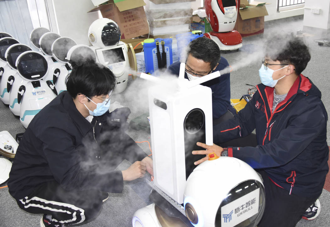 In this photo released by Xinhua News Agency technicians work on a second generation disinfecti ...