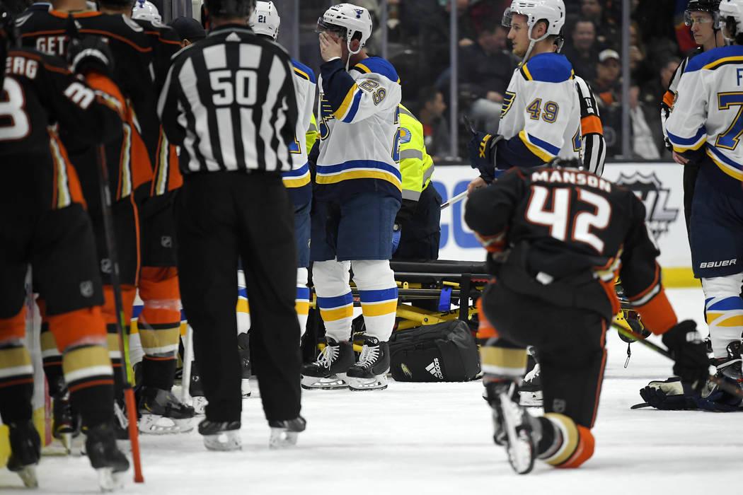 St. Louis Blues defenseman Vince Dunn, left, of center wipes his faces as Anaheim Ducks defense ...