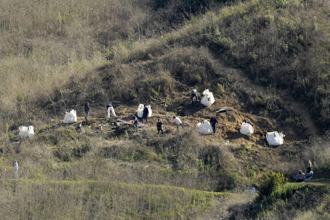 FILE - In this Tuesday, Jan. 28, 2020, file photo, investigators work at the scene of a helicop ...
