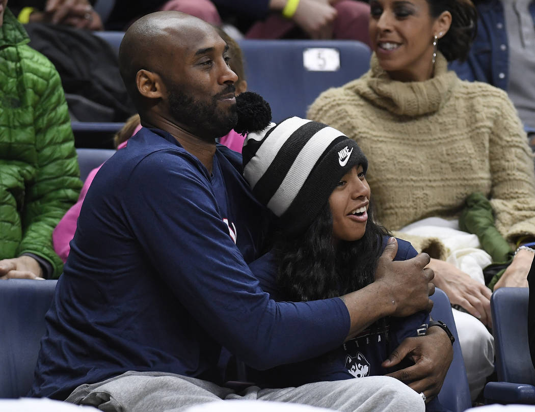 FILE - In this March 2, 2019, file photo Kobe Bryant and his daughter Gianna watch the first ha ...