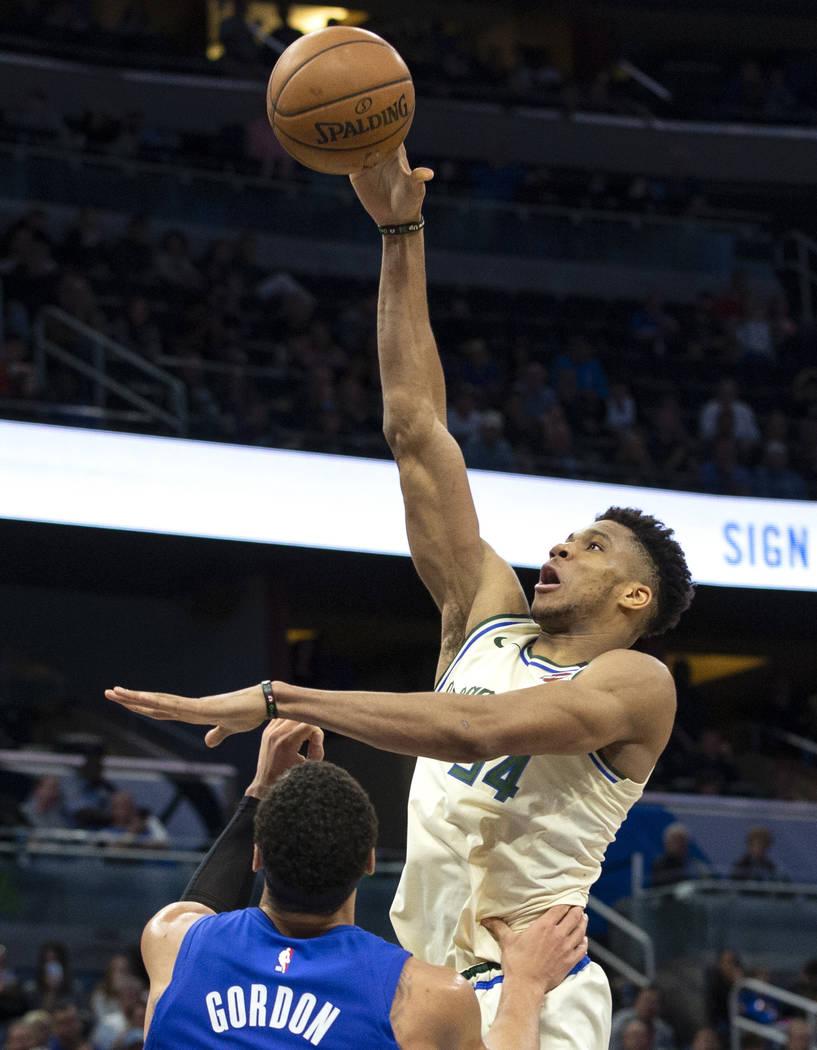 Milwaukee Bucks forward Giannis Antetokounmpo (34) shoots over Orlando Magic forward Aaron Gord ...
