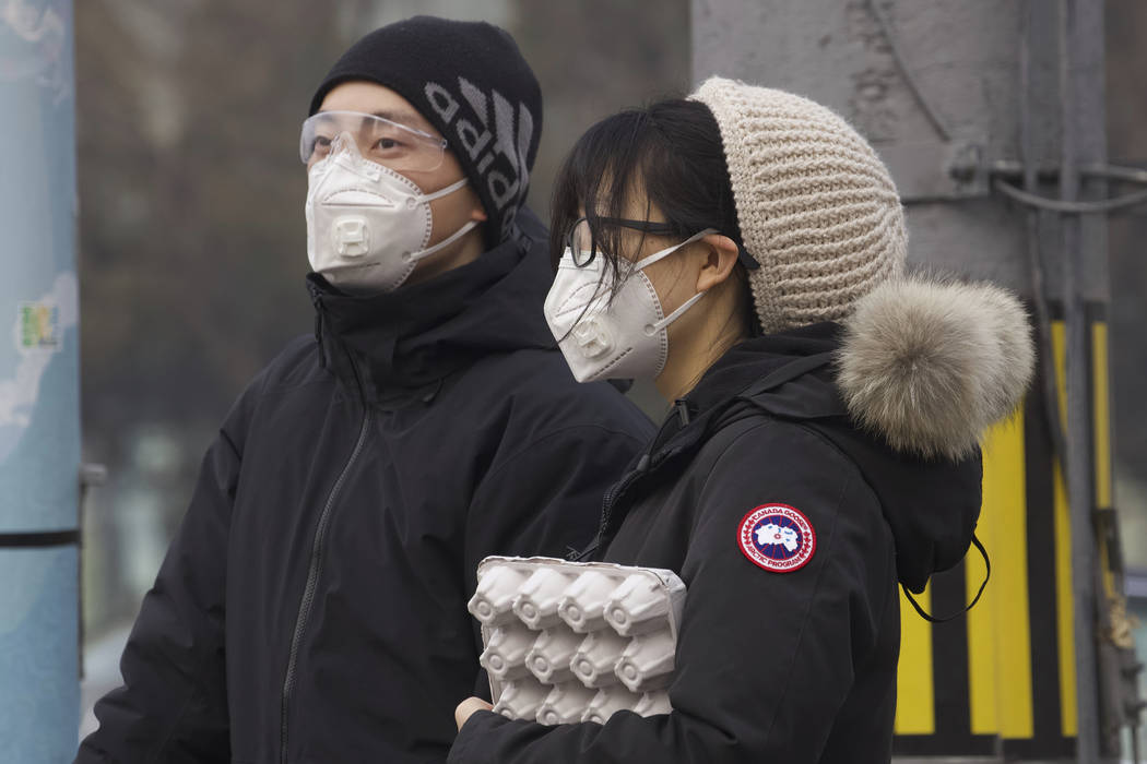 Residents wearing masks wait at a traffic light in Beijing, China Thursday, Feb. 13, 2020. Chin ...