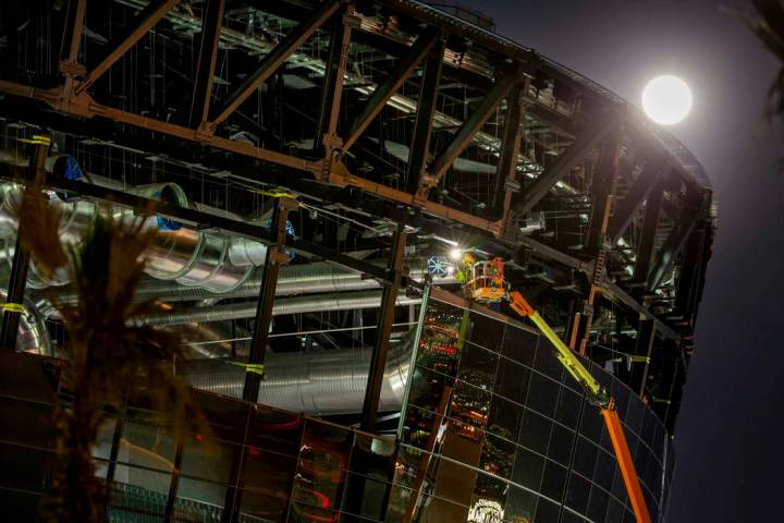 The Snow Moon rises behind Allegiant Stadium as a worked continues welding on the structure on ...