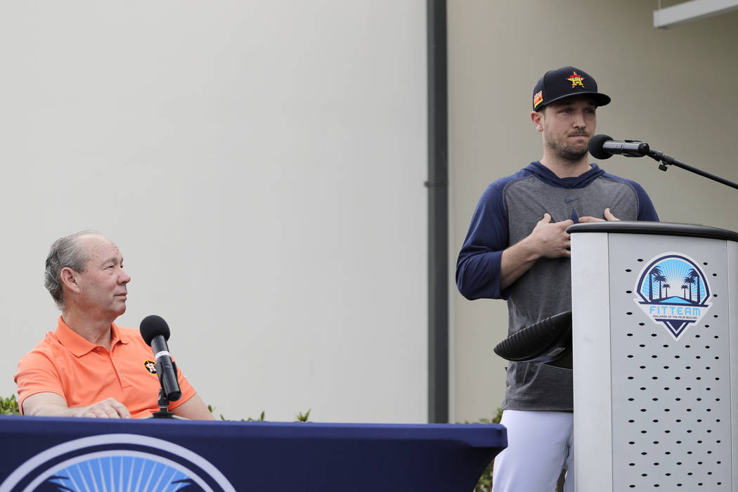 Houston Astros' Alex Bregman, right, delivers a statement as Astros owner Jim Crane listens dur ...